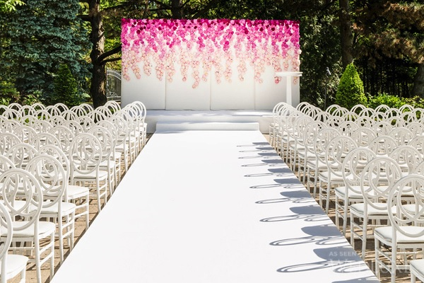 Pure beauty – a crisp chalk white event carpet leads to a stunning floral display
