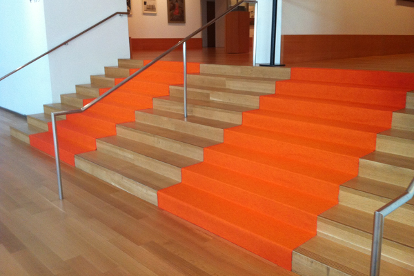 Orange event carpet runner installed on stairs