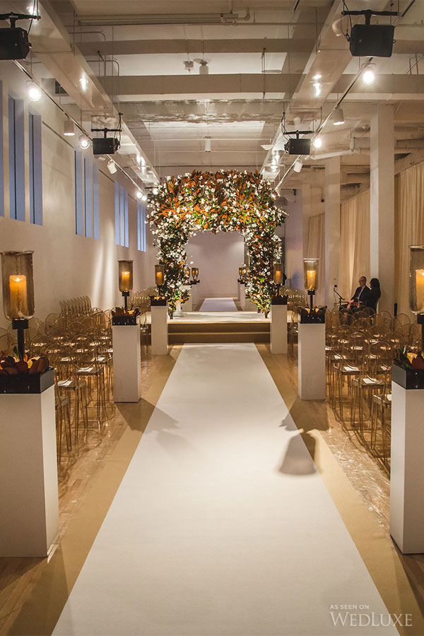 A show-stopping floral chuppah at a wedding, using chalk event carpet to define the space