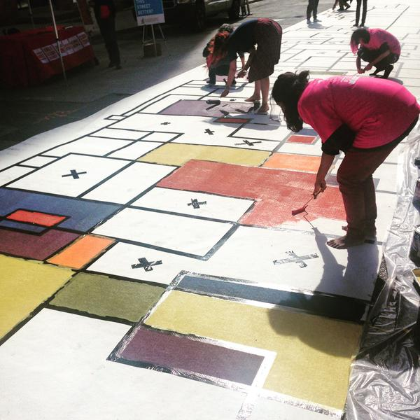 A chalk carpet becomes the canvas for a Mondrian-inspired community art work