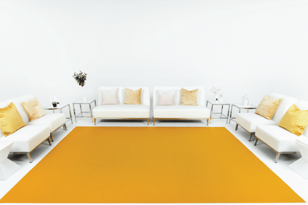 Mustard event carpet installation with white rental furniture and props